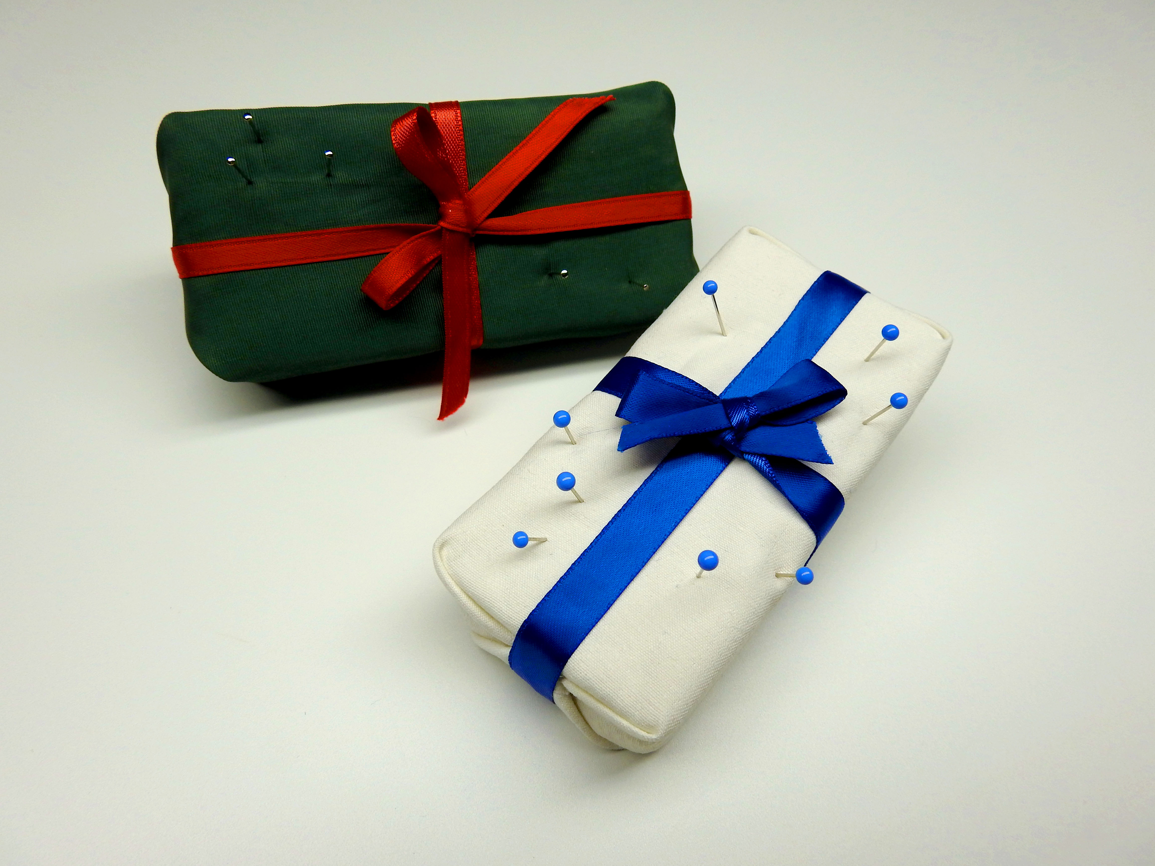 Two finished gift box pin cushions with pins stuck in them. One is white with a deep blue ribbon (winter,) the other is green with a red ribbon (joyful.)